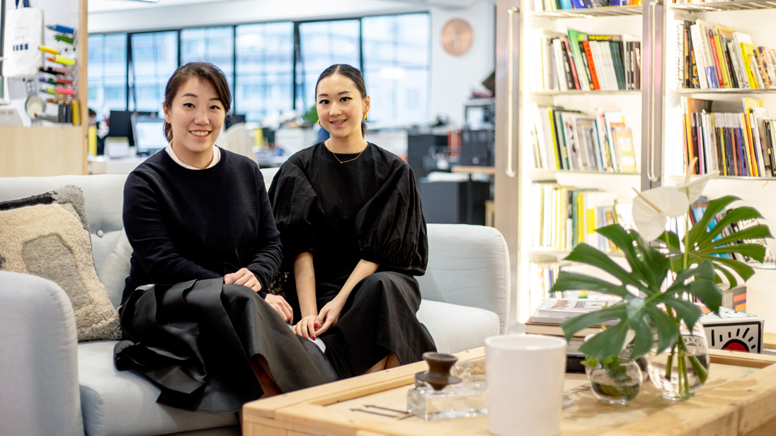 Design duo Jacqueline Chak and Genevieve Chew in their Wong Chuk Hang space. Jacqueline wears a skirt from their fashion brand, EDIT, and Genevieve wears an EDIT dress. Tom Dixon cushion available from Lane Crawford