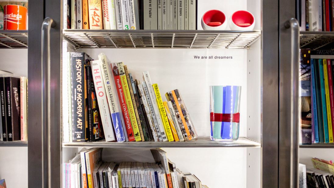 A brightly painted Carlo Moretti Almor Vase from Lane Crawford Home perches on the studio's impressive book wall