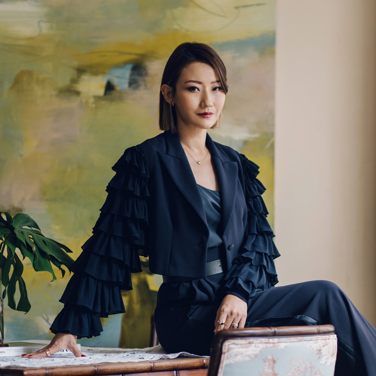Maison Es founder Esther Sham perches on a mahjong table-turned-desk in her elegant Tai Hang home