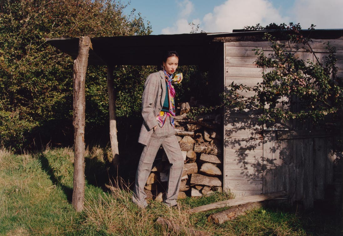 A model in a pant suit poses next to a pile of logs