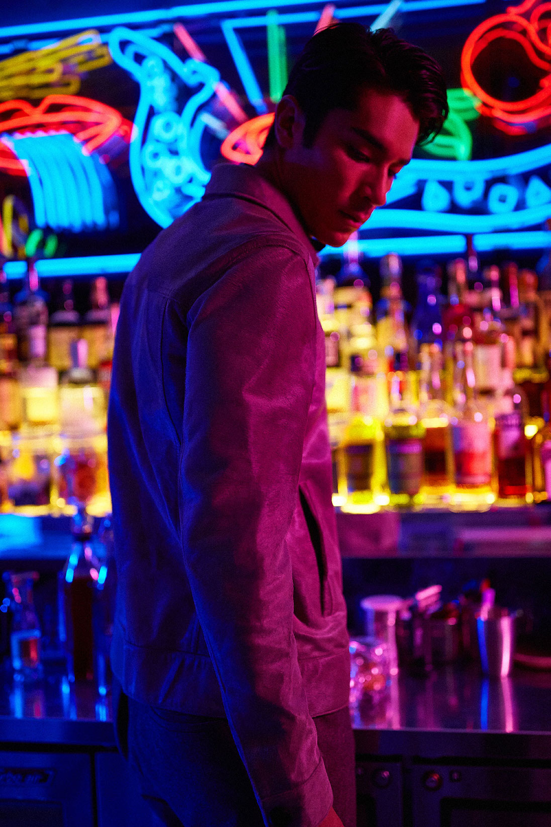 A model stands at a neon-lit bar wearing Salvatore Ferragamo and Hermès
