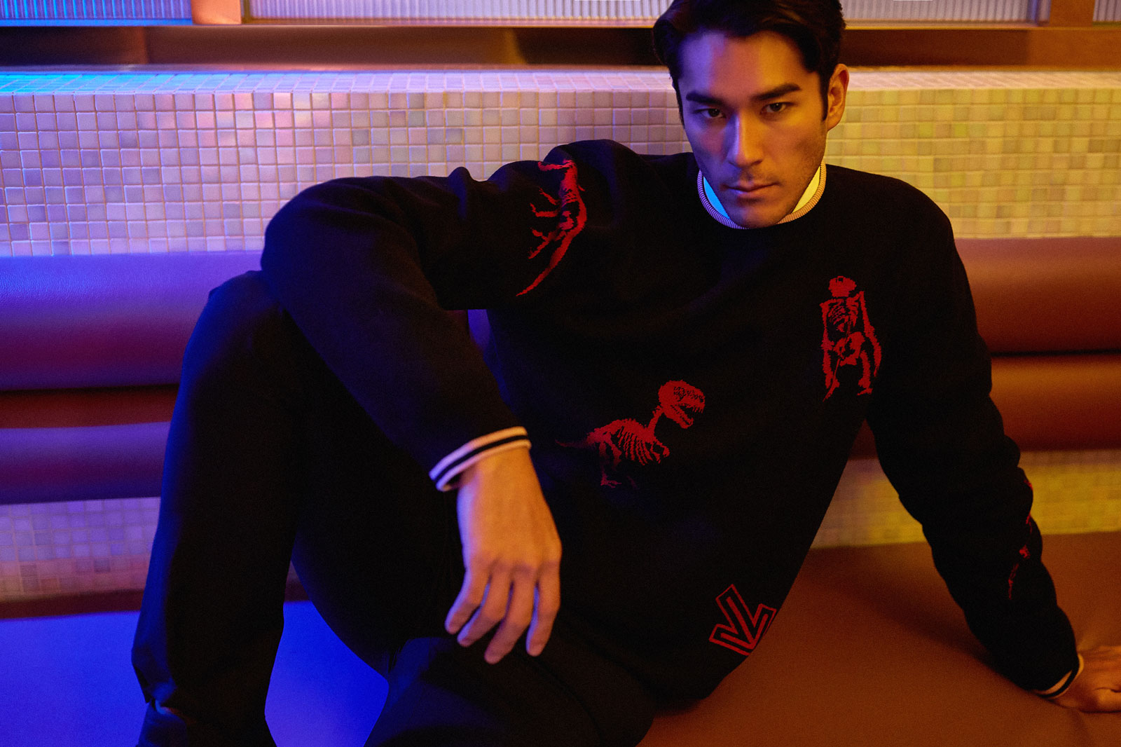 A model lounges on the seats of a diner wearing a dinosaur motif Lanvin sweater