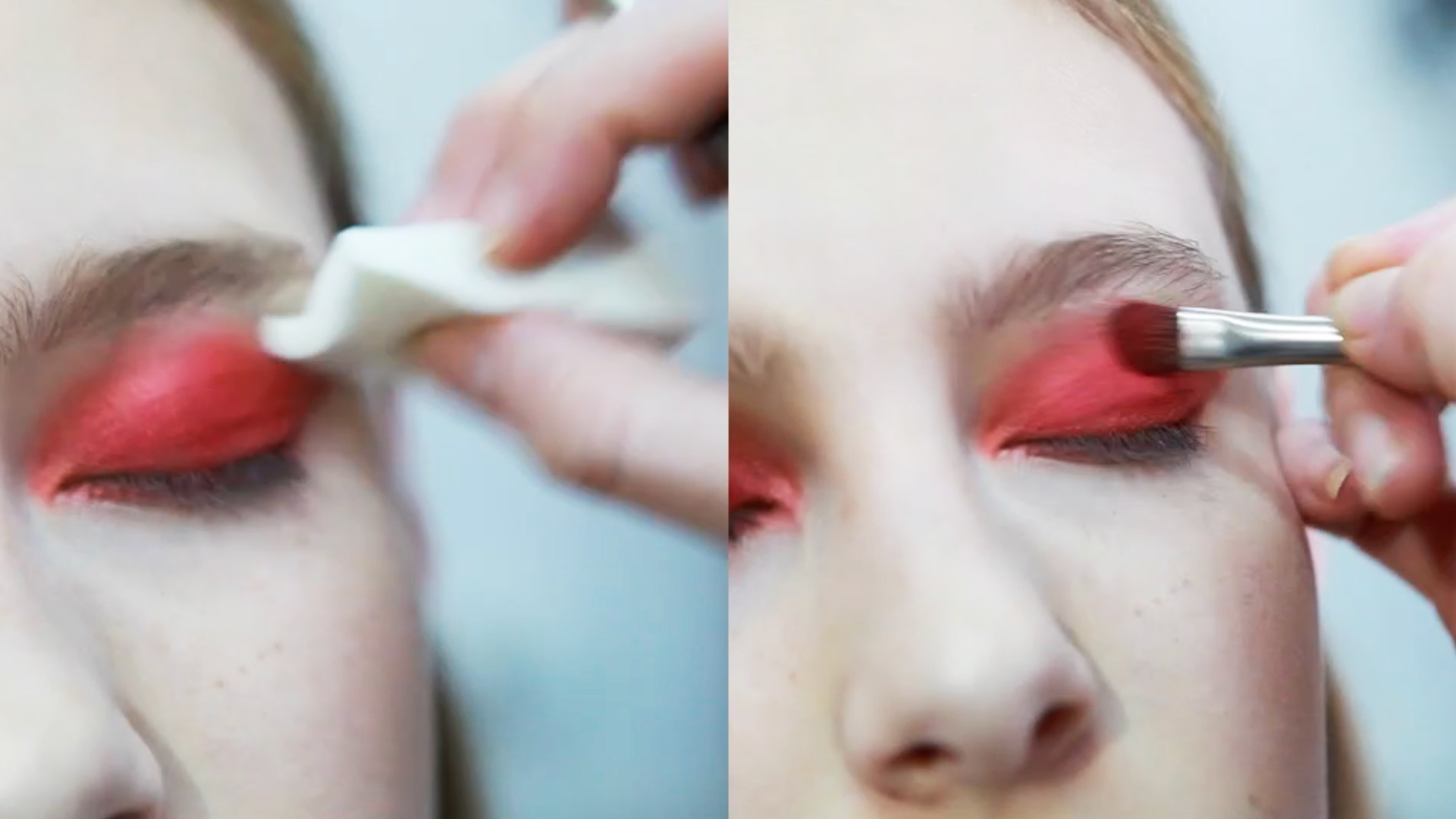 A makeup artist applies bright red eyeshadow to a model