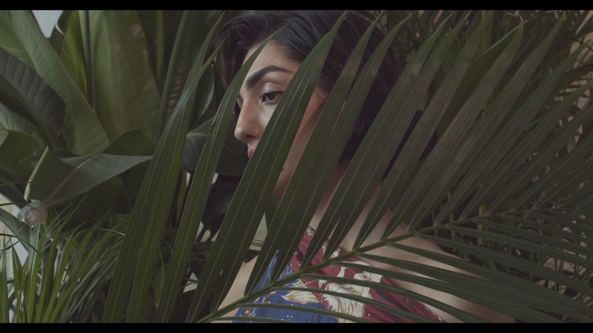 A model is partly obscured by a tropical plant