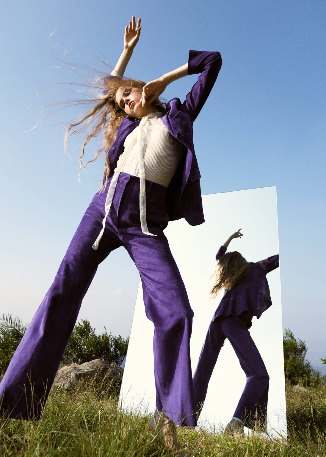A model poses in front of a mirror on a grassy hill wearing a purple Salvatore Ferragamo suit