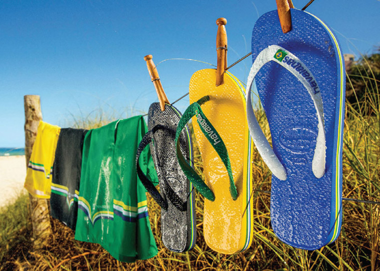 Havaianas hanging on a fence at a beach